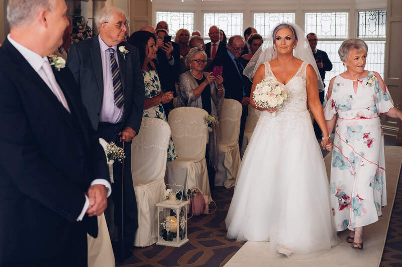Bride and mother walk towards the groom as family look on as civil ceremony begins in Bishops Gate Hotel, Derry