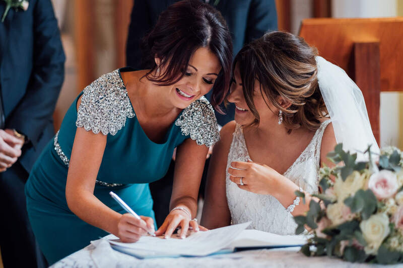 Bride and Bridesmain laugh together while signing the wedding register