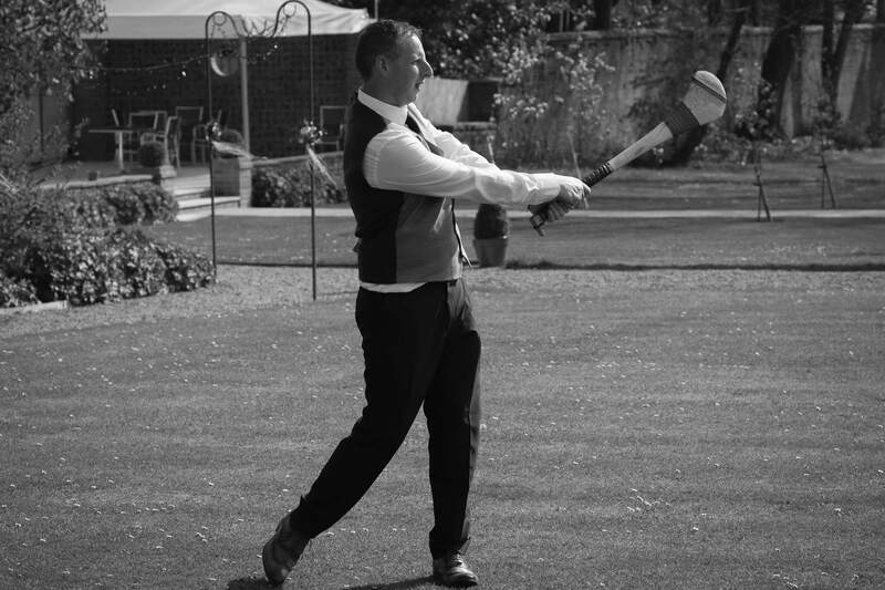 The groom enjoys a bit of hurling in Ballyscullion Park Wedding Venue, Bellaghy County Derry
