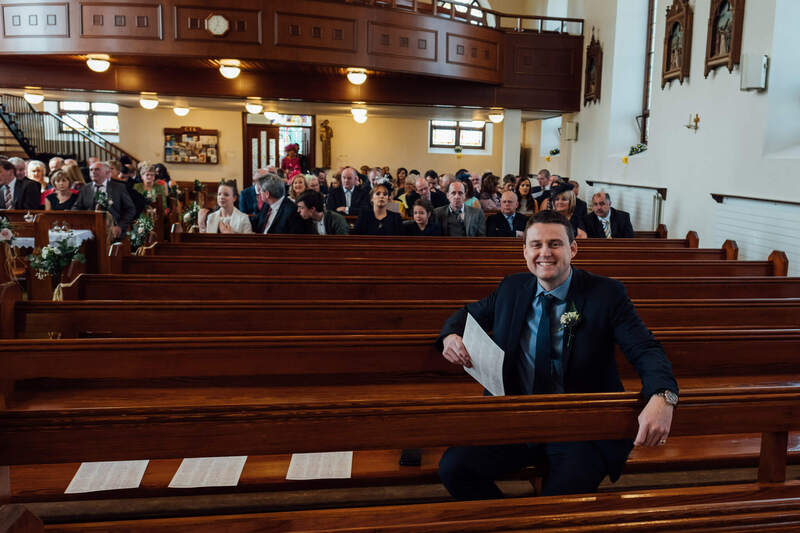 All the cool kids sit at the back! Empty pews in church as everyone sits in the back few rows prior to a Ballyscullion Park Wedding