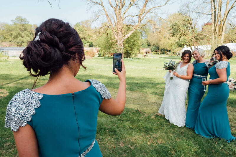 Bridesmaid Photogapher takes a photo of the rest of the bridal party in Ballyscullion Park Wedding Venue.