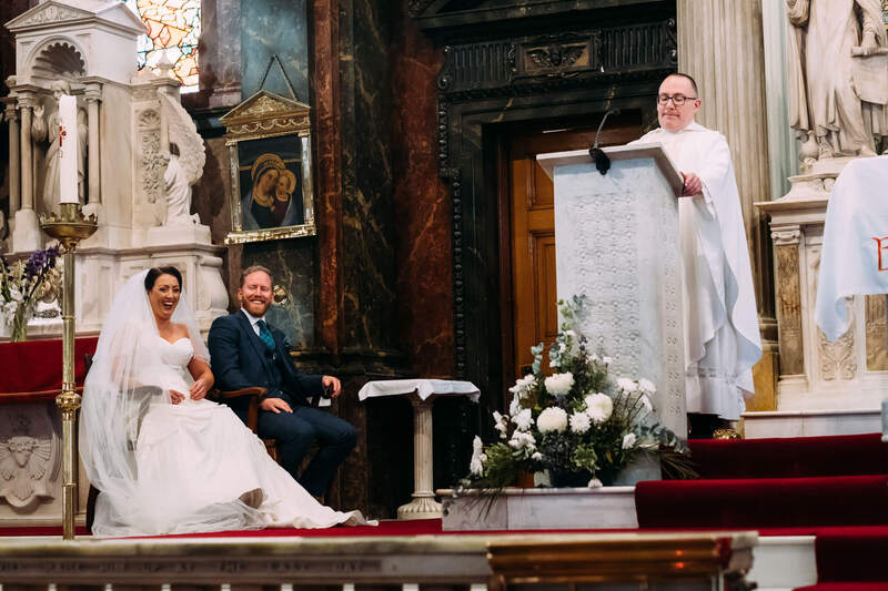 Bride and Groom laugh at Father Chris Ferguson's homily in Long Tower Chapel, Derry, during the wedding ceremony