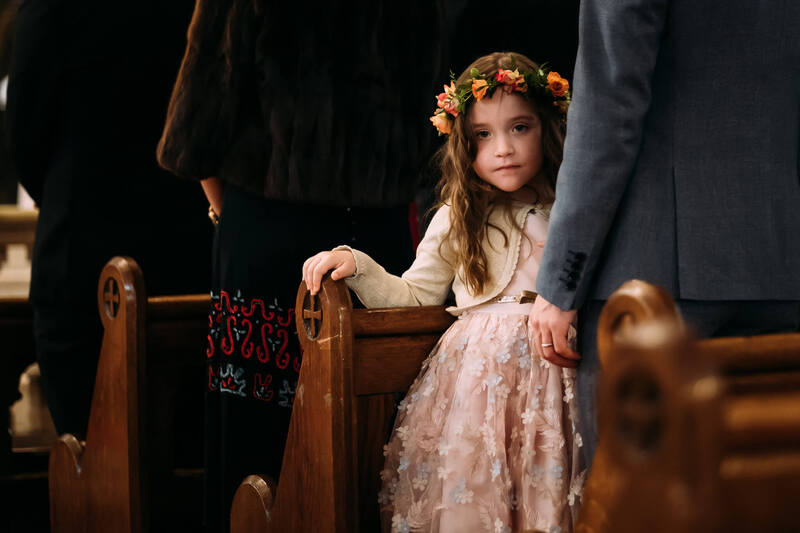 A young girl watches the photographer during the wedding ceremony in Long Tower Chapel, Derry