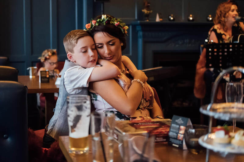 Bridesmaid & Page Boy (mum & son) hug during the wedding reception at Bishops Gate Hotel, Derry