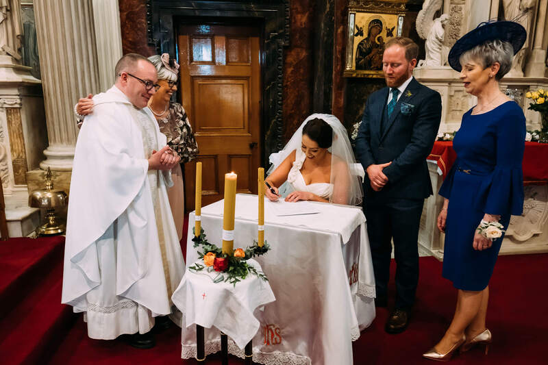 Signing the registrar after the Long Tower Chapel wedding before heading to nearby Bishops Gate Hotel for the reception.