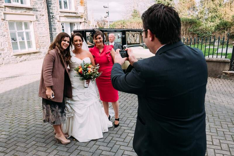 Guests posing for a photo with the bride outside Long Tower Chapel. Derry.