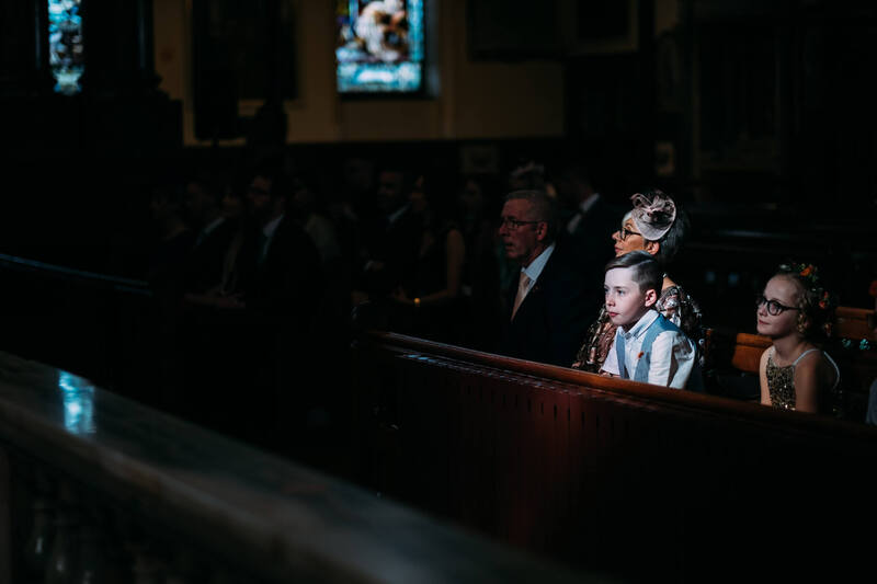 A young boy watches the wedding ceremony from the pews of Long Tower Chapel, Derry