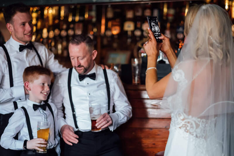 A bride is candidly photographed while she takes a photo on her mobile phone of the Groom, Groomsman and Page Boy in The Drift Inn, Buncrana