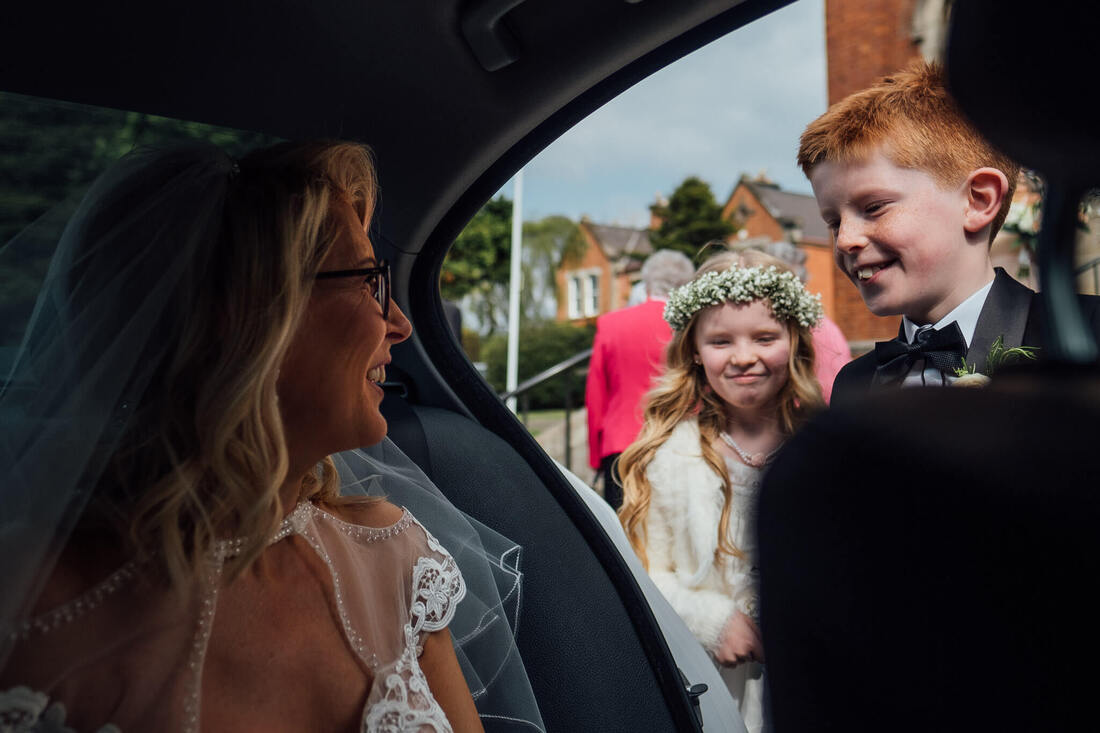 A natural and candid photograph of Page Boy & Flower girl greet their mum, and the Bride as she arrives in the wedding car prior outside St Patrick's Chapel, Derry, Northern Ireland, before their reception at the Inishowen Gateway Hotel, County Donegal, Ireland,