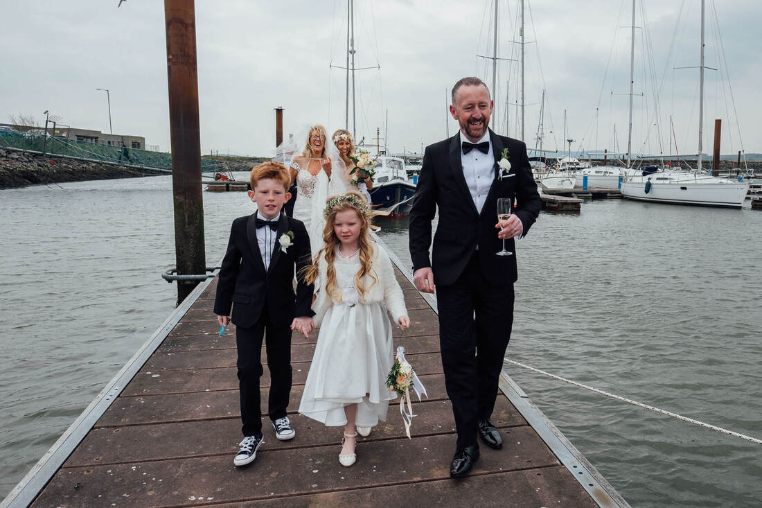 A candid wedding photograph of Des, Laura & Family stop at Fahan Marina on their Wedding Day while travelling between their wedding service at St Patrick's Chapel, Derry, Northern Ireland and their reception at The Inishowen Gateway Hotel, Buncrana, County Donegal