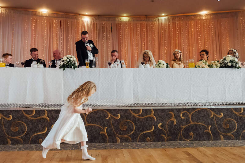 The Best Man making his wedding day speech alongside the Bride & Groom... while the Flower Girl runs across the front of the top table in The Inishowen Gateway Hotel, Buncrana, Donegal, Ireland.