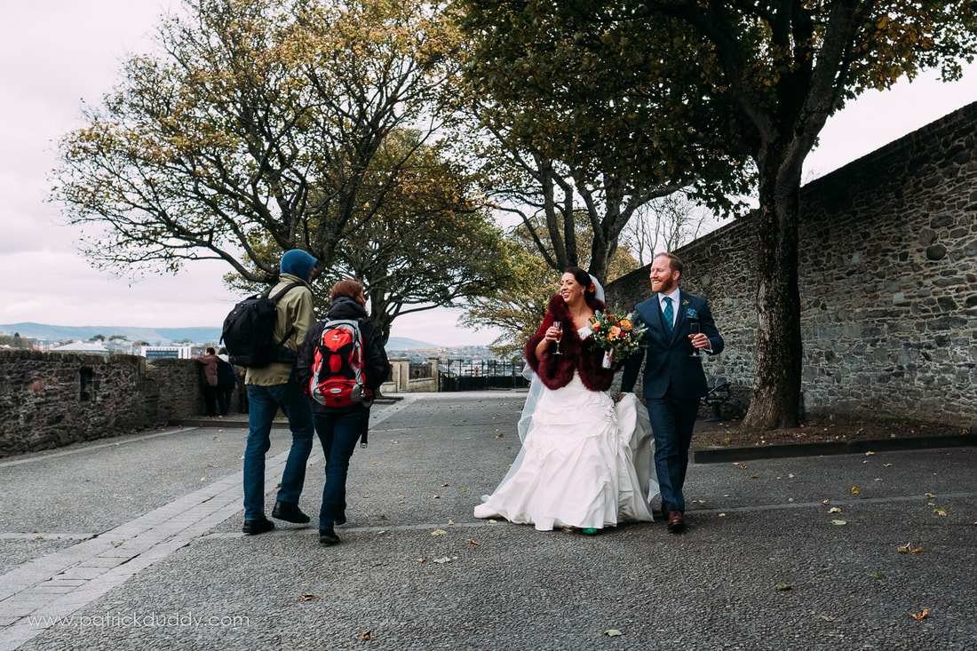 A candid wedding photograph of Caireen & Ronan on Derry's Wall while moving from St Columba's Long Tower Chapel to Bishop's Gate Hotel on their Wedding Day, documented by Patrick Duddy Documentary Wedding Photography