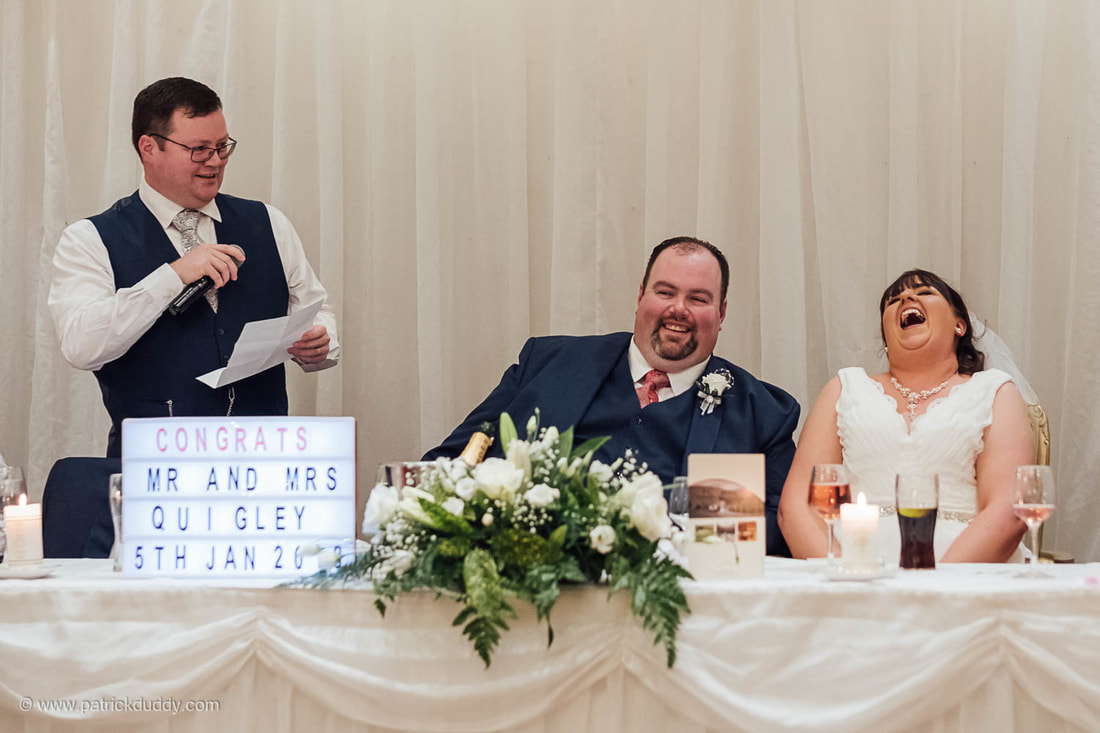 Michelle & Jonathan, bride and groom, laugh at the Best Man's speech during their civil ceremony wedding day at An Grianan Hotel, Burt, County Donegal, Ireland by Patrick Duddy Documentary Wedding Photography, Derry, Northern Ireland.