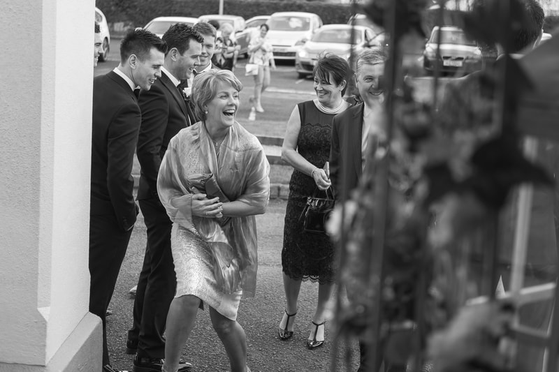 A wedding guest shows her excitement when everyone starts to arrive at the church prior to the wedding ceremony.