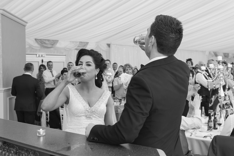 The bride and groom knock back a couple of drinks on the way to the top table in Ballyscullion Wedding Venue.